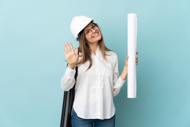 Arquitecto eslovaco chica sosteniendo planos aislados sobre fondo azul saludando con la mano con expresión feliz