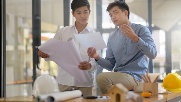 El arquitecto explica el concepto de diseño de la casa al ingeniero supervisor del proyecto.