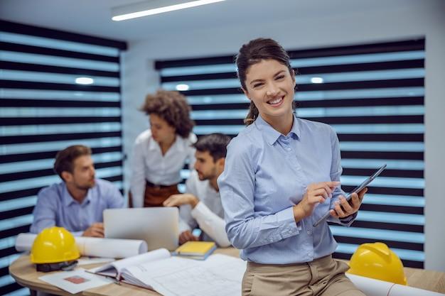 Arquitecto femenino sonriente sentado en una mesa en la oficina y usando tableta mientras mira a la cámara