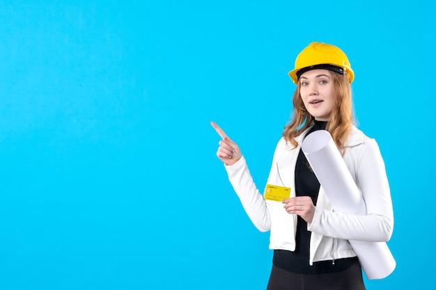 Arquitecto femenino de la vista frontal que sostiene el plan y la tarjeta bancaria en el azul