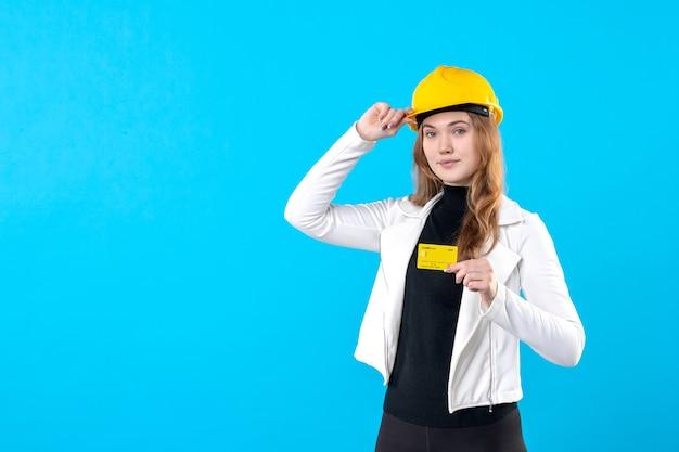 Arquitecto femenino de vista frontal con tarjeta bancaria en azul