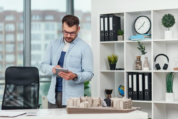 Arquitecto guapo trabajando en un proyecto de construcción utilizando tecnologías de innovación. hombre caucásico con tablet pc en la oficina.