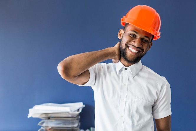 Arquitecto hombre afroamericano de pie contra la pared azul en el lugar de trabajo