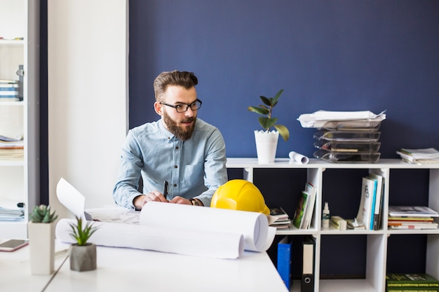 Arquitecto hombre joven con blueprint en la mesa en el lugar de trabajo
