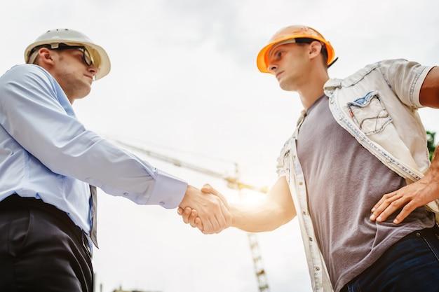 Arquitecto ingeniero estrecharme la mano en el sitio de construcción. trabajo en equipo empresarial, cooperación, concepto de colaboración de éxito