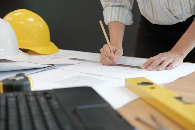 Arquitecto ingeniero que trabaja en el plano de la casa del proyecto inmobiliario en el lugar de trabajo.
