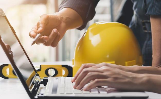 Arquitecto ingeniero trabajando concepto y herramientas de construcción o equipo de seguridad en la mesa.