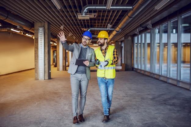 Arquitecto innovador dedicado que sostiene la tableta y explica sus ideas al trabajador de la construcción. edificio en interior del proceso de construcción.