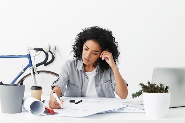 Arquitecto jefe femenino de raza mixta concentrada sentirse frustrado, sentado en el escritorio blanco