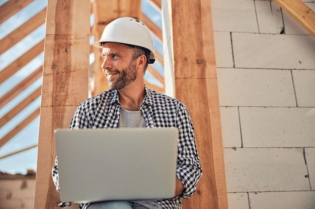 Arquitecto joven alegre usando su computadora portátil al aire libre