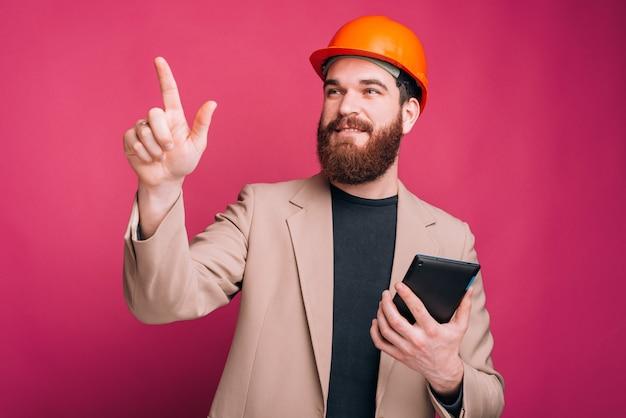 Arquitecto joven y guapo apuntando lejos y sosteniendo la tableta en la mano