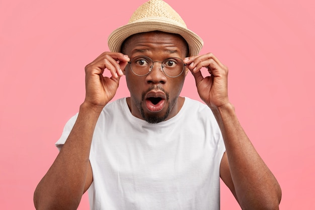Arquitecto masculino aturdido de raza mixta en sombrero de paja