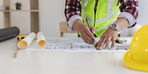 El arquitecto masculino está dibujando en los planos de la casa, está revisando los planos de la casa que ha diseñado antes de enviarlos a los clientes, está diseñando la casa y el interior. ideas de diseño para el hogar.