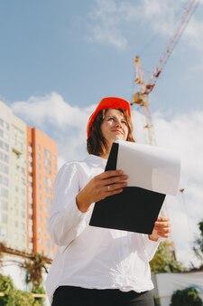 Arquitecto de la mujer hermosa joven en camisa blanca y casco que sostiene un tablero del tirón. mujer con casco en un sitio de construcción en casa.