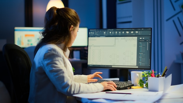 Arquitecto de la mujer que empareja los planes digitales de la pc con los planos que trabajan en horas extras de la oficina de la empresa de puesta en marcha. diseñador que utiliza software cad para diseñar un concepto 3d de edificios que se crean a altas horas de la noche
