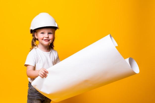 Arquitecto de niña en el casco de construcción con un cartel aislado en la pared amarilla