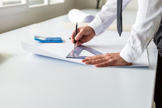 Arquitecto o diseñador que trabaja en un proyecto dibujando una línea a lo largo de una regla en una oficina luminosa.