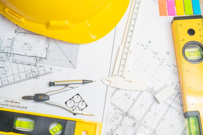 Arquitecto o planificador trabajando en dibujos para planos de construcción en una mesa