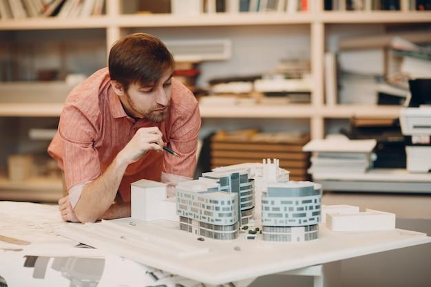 Arquitecto con planos y proyecto de diseño de diseño en la oficina