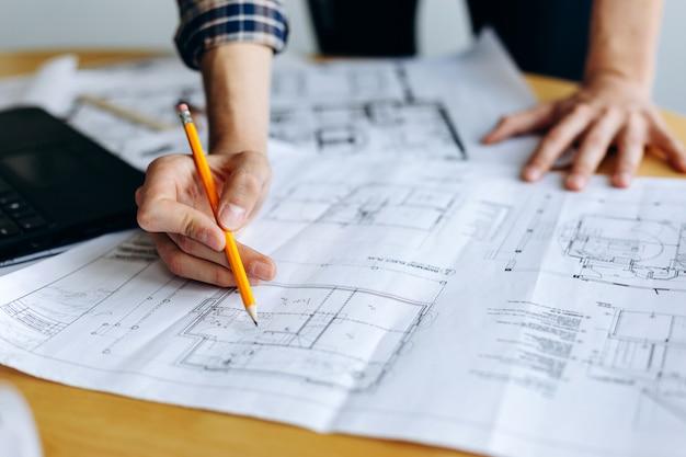 Arquitecto con pluma con dibujos en construcción sobre planos en oficina
