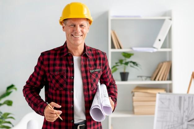 Arquitecto posando mientras sostiene sus planes