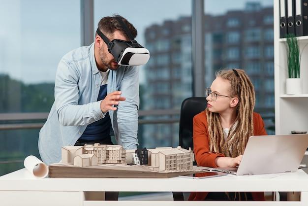 Arquitecto profesional masculino en gafas de realidad aumentada trabajando con maqueta de edificio y compañera de trabajo con laptop