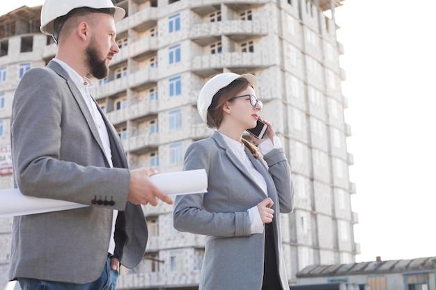 Arquitecto profesional de la mujer que habla en el teléfono móvil que se coloca con su colega masculino en el emplazamiento de la obra