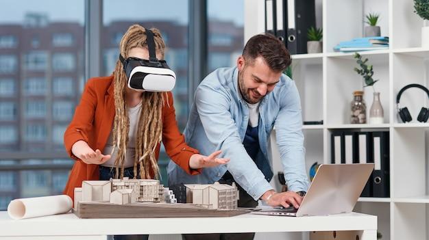 Arquitecto profesional que trabaja en el escritorio de la oficina y con un visor de realidad virtual, está viendo una interfaz de realidad virtual