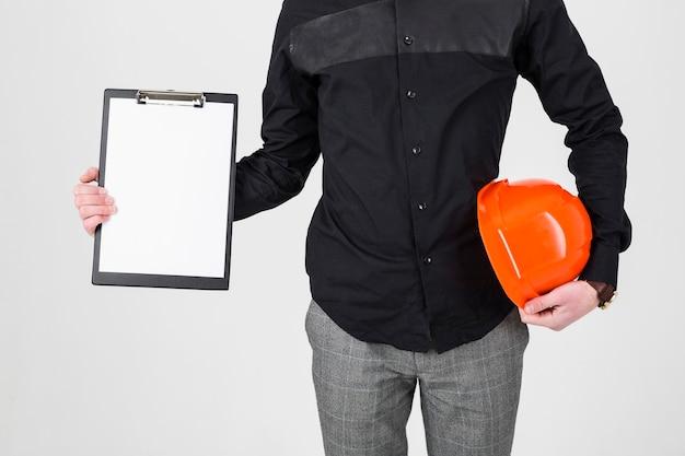 Un arquitecto que sostiene el tablero y el casco de protección sobre el fondo blanco