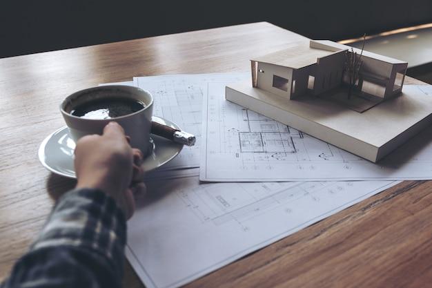Un arquitecto que trabaja en un modelo de arquitectura con papel de dibujo de la tienda mientras bebe café