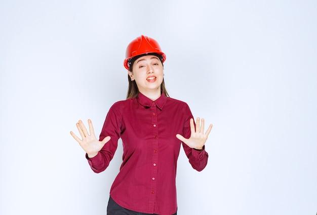 Arquitecto de sexo femenino hermoso en casco duro rojo que mira la cámara sobre la pared blanca.