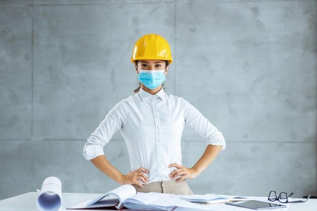 Arquitecto de sexo femenino con mascarilla y casco de pie con las manos en las caderas