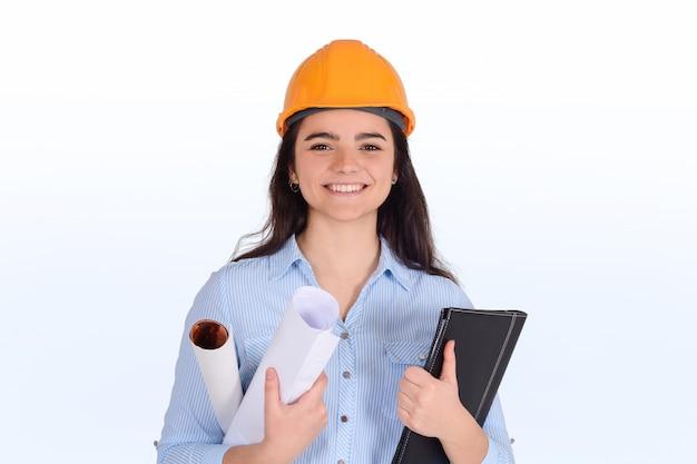 Arquitecto de sexo femenino que sostiene carpetas y planos.