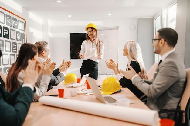 Arquitecto de sexo femenino en ropa formal de pie y hablando de un proyecto importante. colegas sentados y aplaudiendo. interior de la sala de juntas.