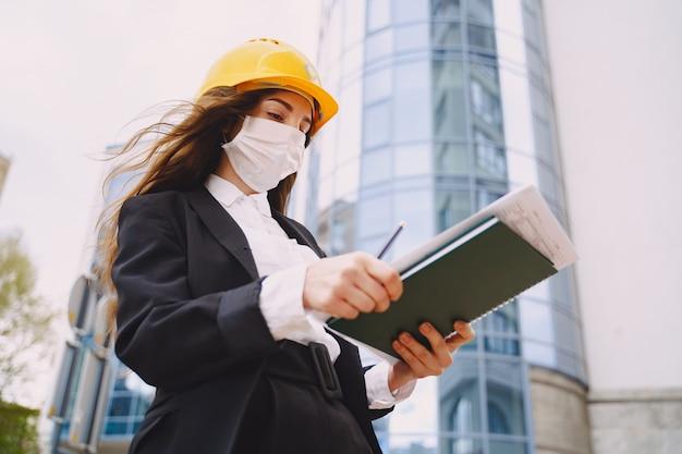 Arquitecto de sexo femenino con el sitio de construcción en el