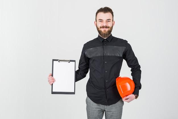 Arquitecto de sexo masculino joven sonriente que sostiene el hardhat y el tablero