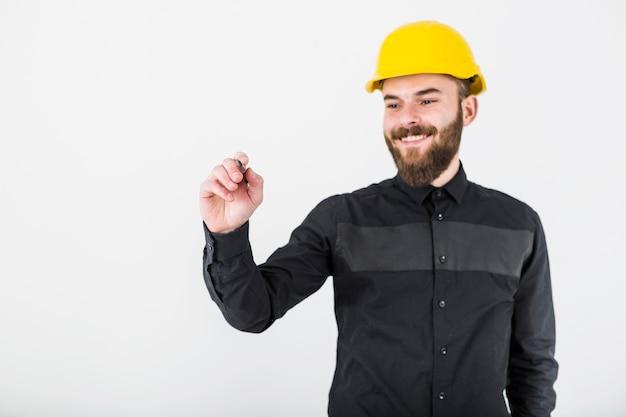 Un arquitecto de sexo masculino sonriente que lleva la pluma de tenencia amarilla del casco de protección para escribir