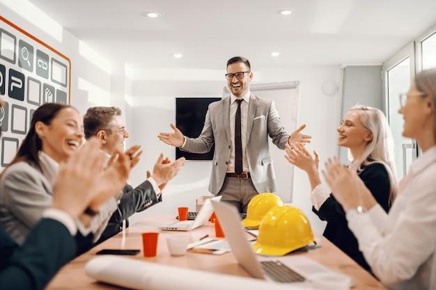 Arquitecto sonriente en ropa formal terminando el discurso sobre nuevo proyecto colegas sentados y aplaudiendo.