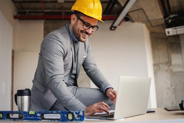 Arquitecto sonriente sentado en el escritorio en el sitio de construcción y usando la computadora portátil para mejorar el proyecto