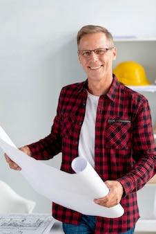 Arquitecto sonriente sosteniendo sus planes