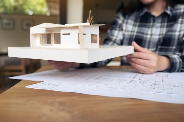 Un arquitecto sosteniendo y trabajando en el modelo de arquitectura con papel de dibujo de la tienda en la mesa