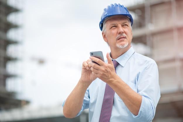 Arquitecto con su teléfono inteligente móvil frente a un sitio en construcción