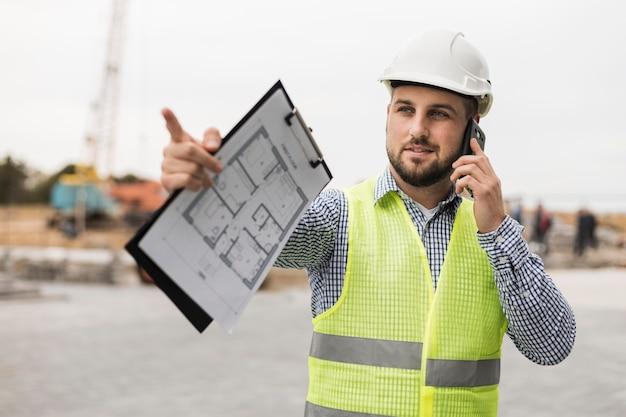 Arquitecto de tiro medio hablando por teléfono