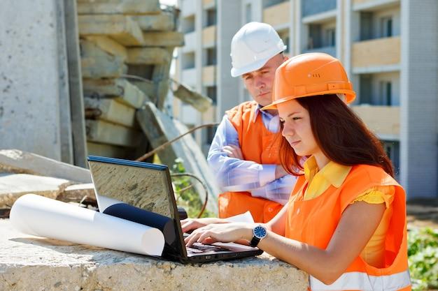 Arquitecto y trabajador de la construcción femenina mirando portátil juntos contra la construcción