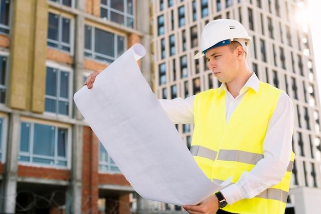 Arquitecto de vista lateral con chaleco de seguridad y planos