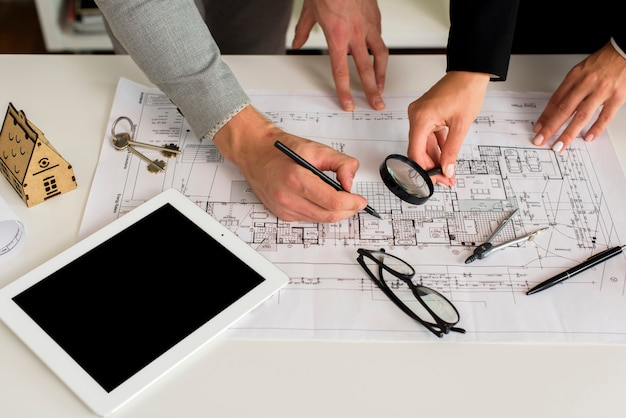 Arquitectos analizando plan con maqueta de lupa