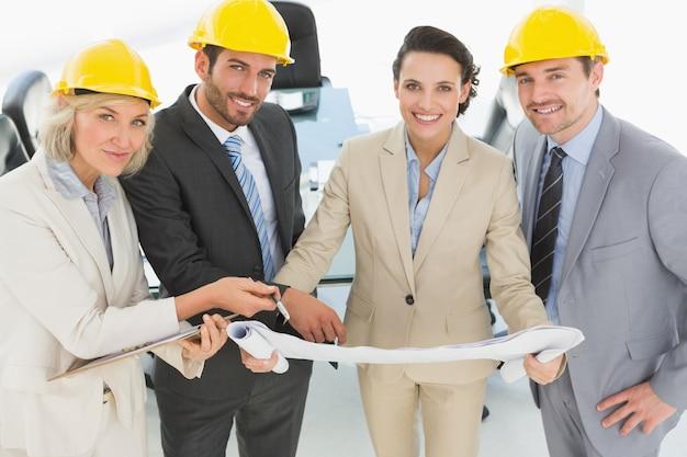 Arquitectos bien vestidos con cascos y planos