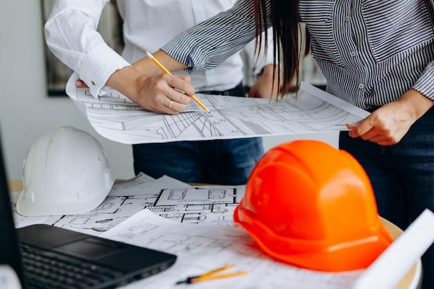 Arquitectos discutiendo en la mesa con blueprint