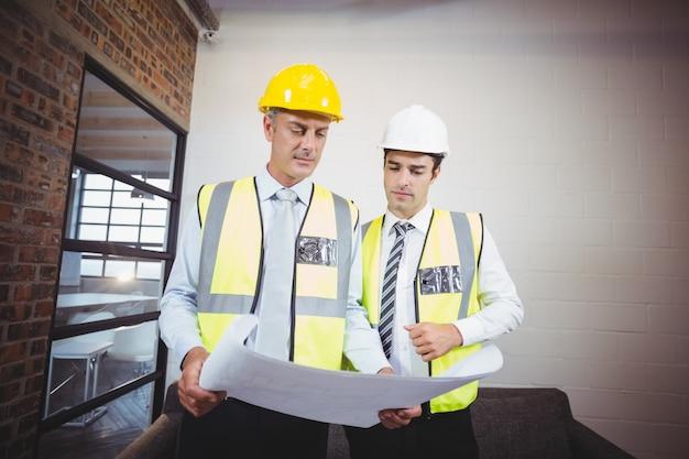 Arquitectos discutiendo mientras sostiene el plano
