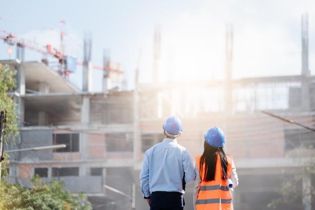 Arquitectos e ingeniero en un sitio de construcción mirando planos y apuntando